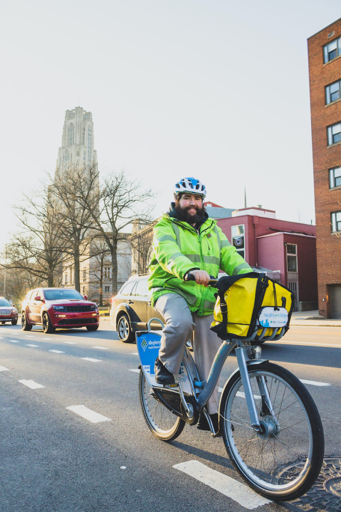 A person in a bright yellow jacket riding a Healthy Ride in an Oakland bike lane